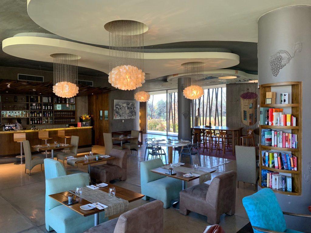 Vista do restaurante e bar do hotel Entre Cielos, com mesas, poltronas, lustres e estante de livros. Foto de Bruno Tavares