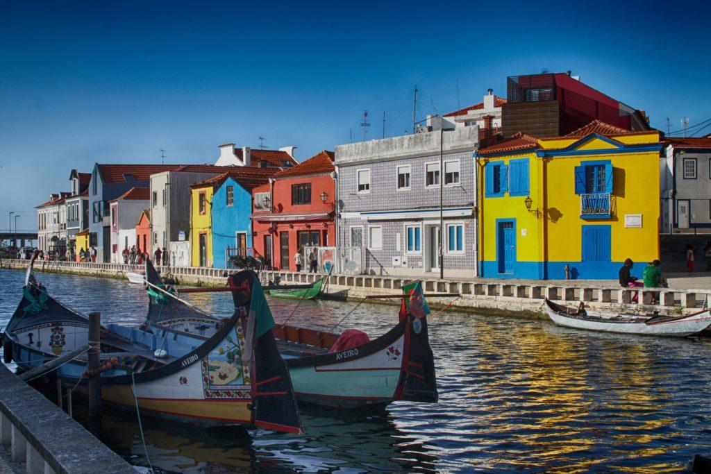 Vista de casinhas coloridas às margens de rio na cidade de Aveiro, em Portugal, com os barcos moliceiros na água. Foto de Luis Núñez via Pexels.