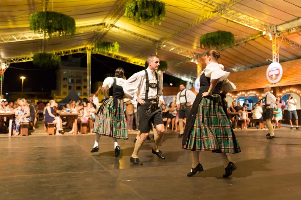 Na imagem vemos um casal dançando em primeiro plano, com trajes típicos alemães. Ao fundo há mais casais e o público que os assiste. É noite e estão em área coberta. Foto do site oficial do Parque.