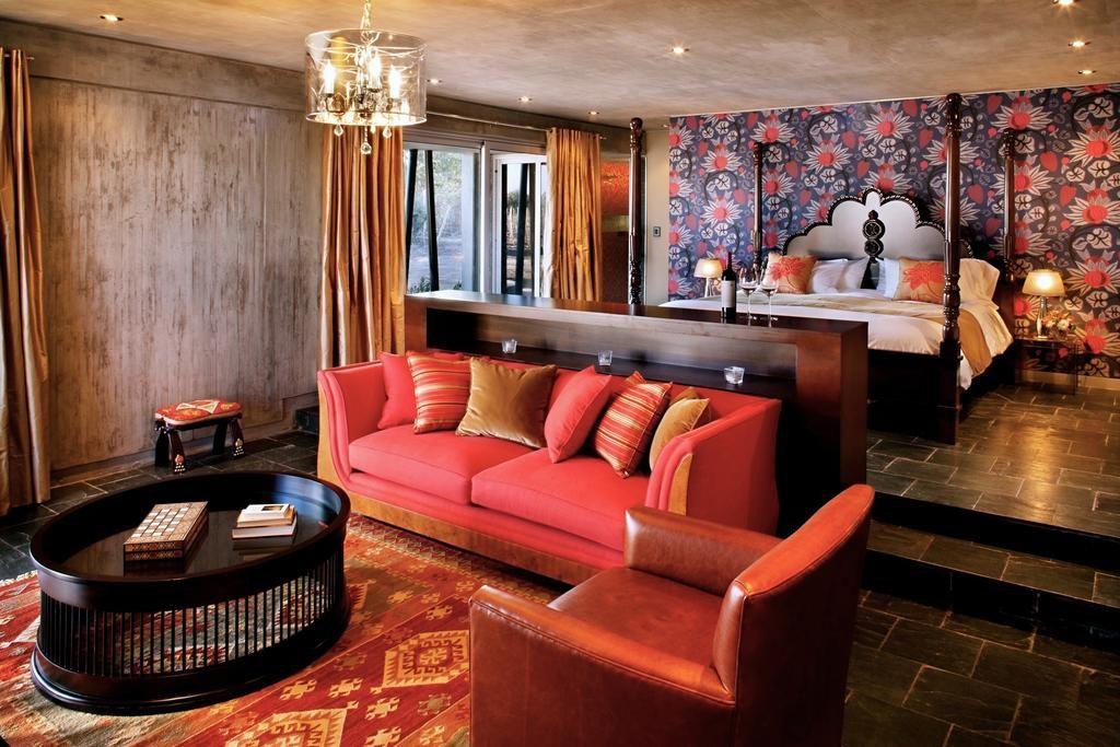 Na imagem vemos a Suíte de Luxo Gran Cru, com cama, sofá, lustre e janela para varanda. Foto: Bruno Tavares
