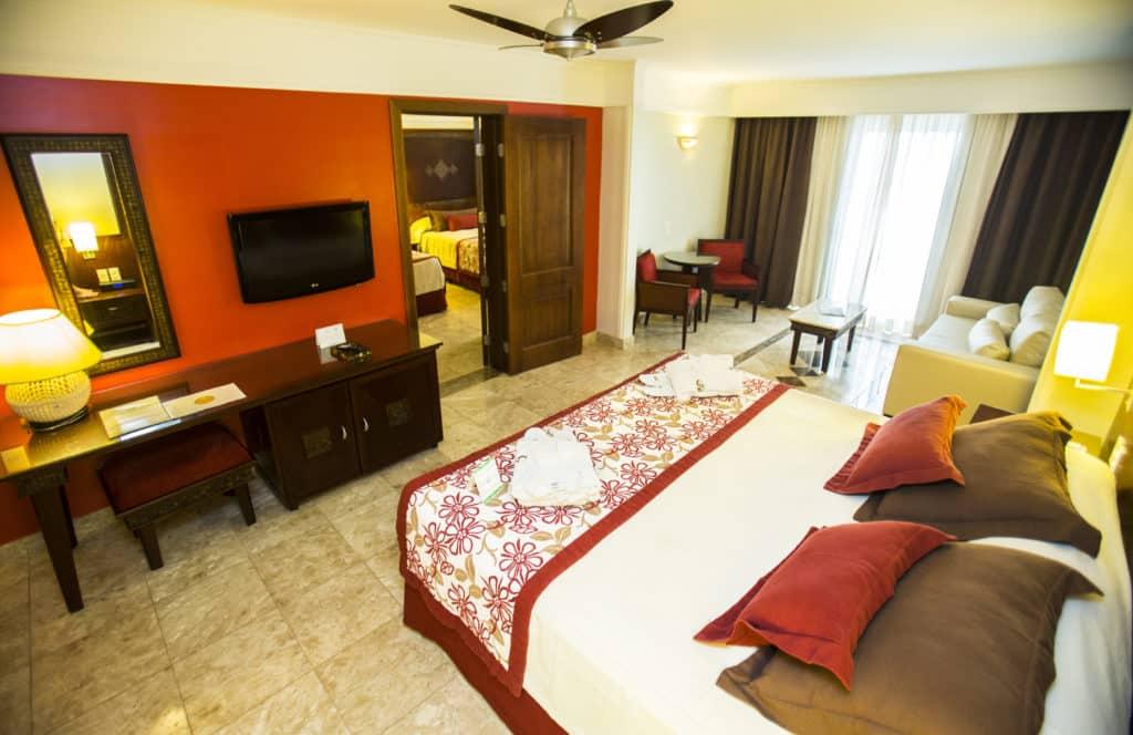 Suite Junior no Grand Palladium Imbassai - cama de casal com vista para o quarto com decoração em detalhes vermelhso
