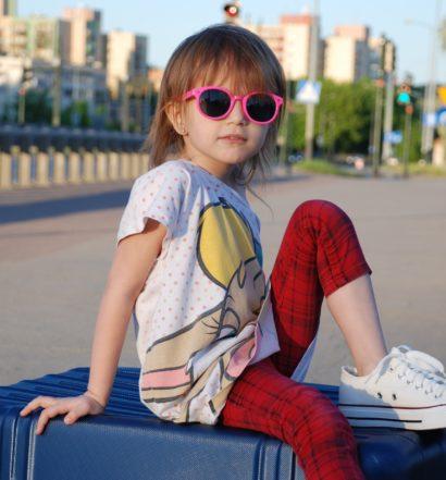 Lugares para viajar com criança - menina em cima da mala