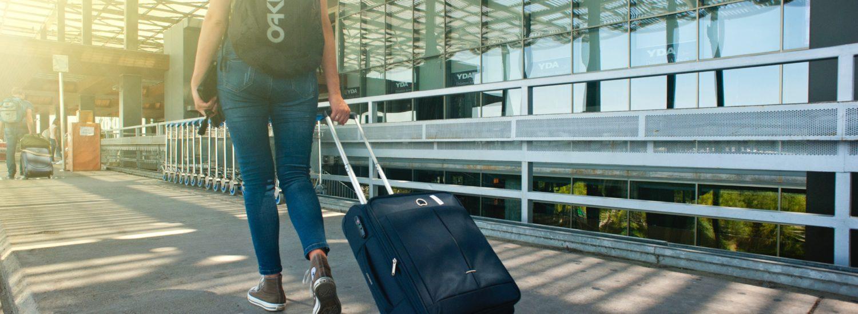 Menina de costas levando a mala no aeroporto viajando pelo mundo - Foto: Oleksandr Pidvalnyi via Pexels