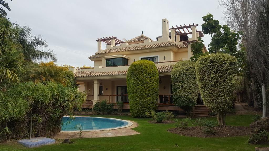 Vista externa do Villa Boutique Banus, piscina redonda com muito verde e propriedade amarela - viajando barata pelo mundo