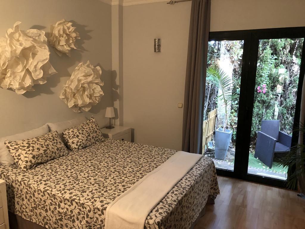 Quarto Junior na Villa Boutique Banus em Marbella. Cama de casal florida com decoração clara e vista para a sacada - viajando barato pelo mundo