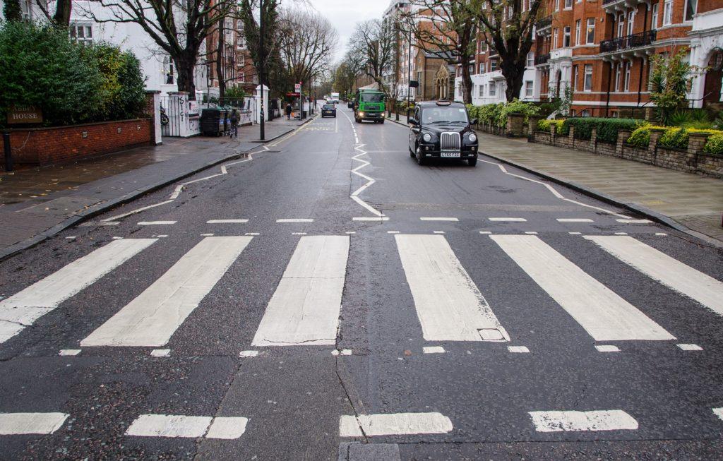 Vista da Abbey Road, rua icônica por ser cenário de capa de um dos discos dos Beatles nos anos 60, com foco para a faixa de pedestres onde a banda foi fotografada - um dos principais pontos turísticos de londres. Foto de Imagem de Rudy and Peter Skitterians via Flickr