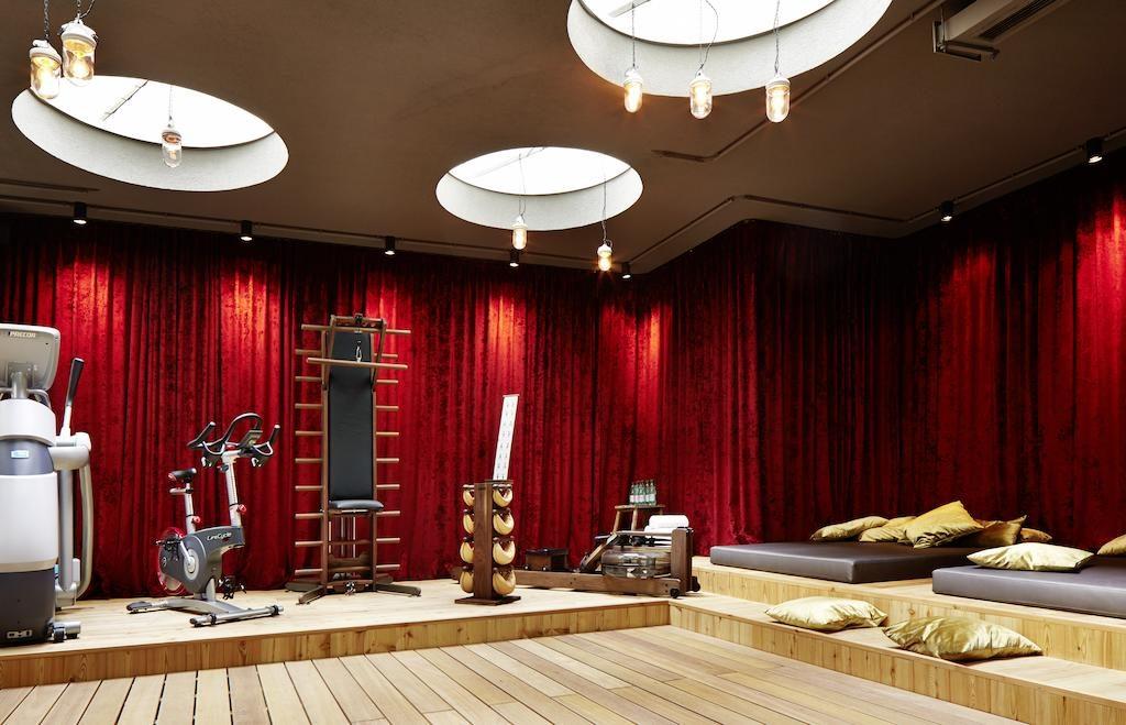 Foto dos equipamentos da academia do 25hours Hotel, em Viena, com cortina de veludo vermelho, e almofadas douradas sobre colchonete marrom.