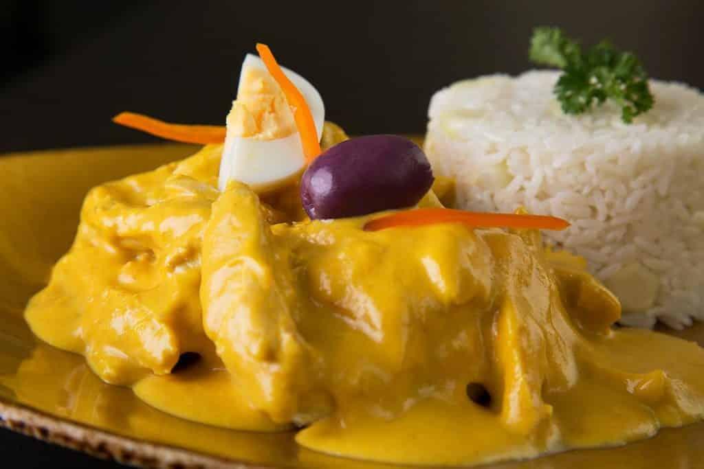 Foto de prato conhecido como ají de gallina, feito pelo chef Gastón Acurio, com frango ao molho, ovo cozido, azeitona preta e arroz.