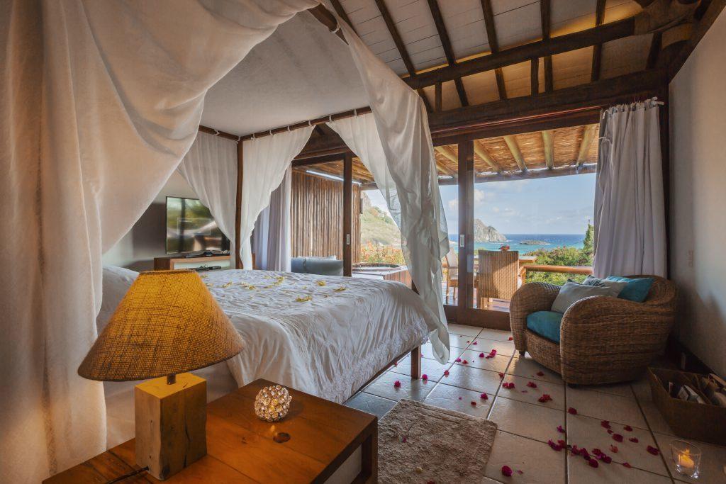 Bangalô com cama ampla, poltrona e pétalas de rosa na Pousada Maravilha