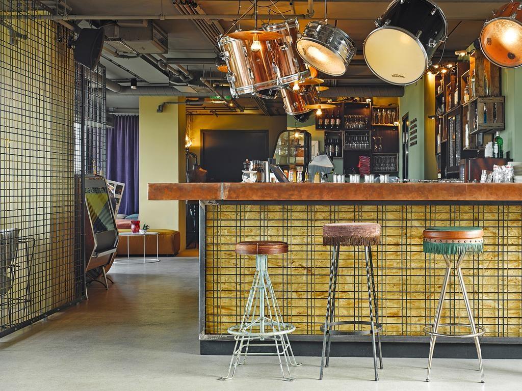Vista de parte do bar do terraço do hotel 25Hours, com partes de bateria na decoração, banquetas e balcão de bebidas.