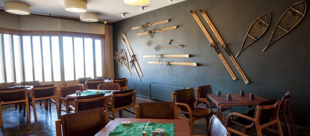 Bar Puerta del Sol, lugar onde comer no Valle Nevado, com parede escura decorada com equipamentos de neve. Foto do site Valle Nevado