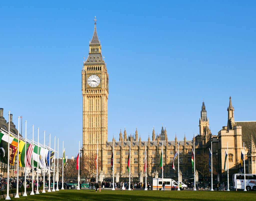 Vista do Big Ben, a famosa Torre do Relógio, em Londres, com bandeiras de diversos países à frente. Foto de Pedro Szekely via Flickr.