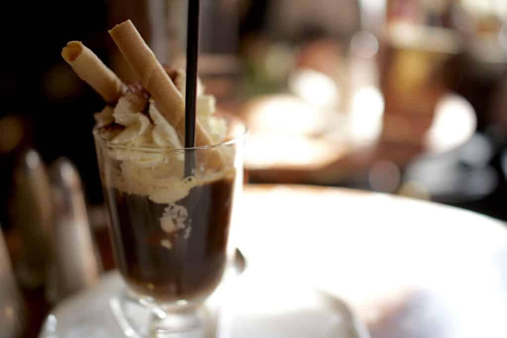 Foto de taça com café/chocolate com chantili e canudos de massa doce, bebida do Cafe Central, de Viena.
