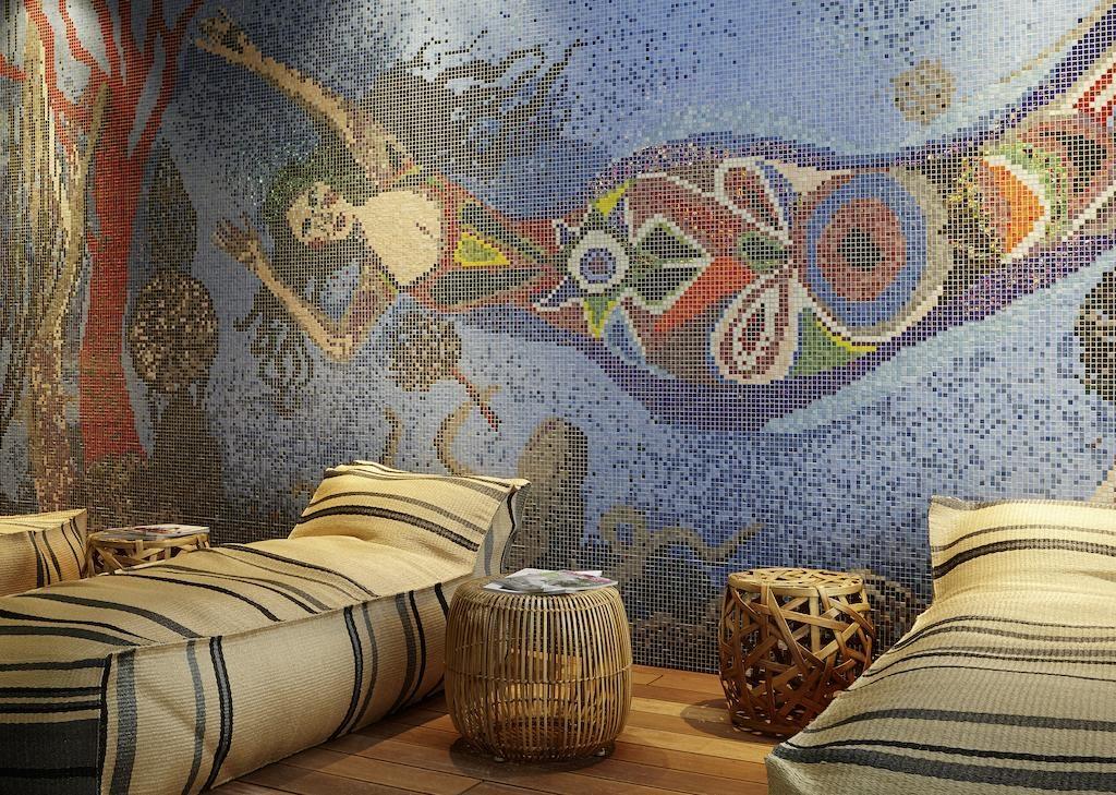 Foto de parede decorada com mosaicos que formam a imagem de uma sereia, em ambiente conhecido como Caverna da Sereia, onde funciona a academia e o spa do hotel.