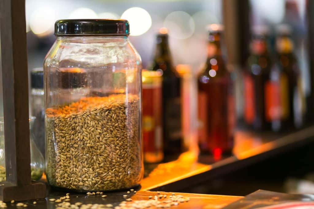 Imagem de pote com cevada em primeiro plano, e garrafas de cerveja desfocadas ao fundo. Foto do site Parque Vila Germânica Blumenau.