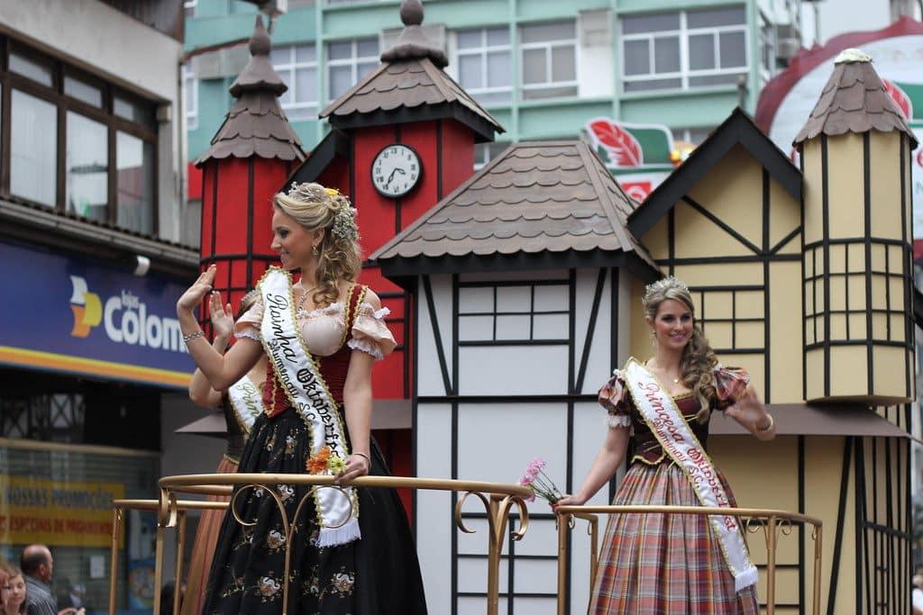 Parte do desfile da Oktoberfest de Blumenau, com carro alegórico de prédios estilo enxaimel, com duas mulheres desfilando. Foto de Vitor Pamplona via Flickr.