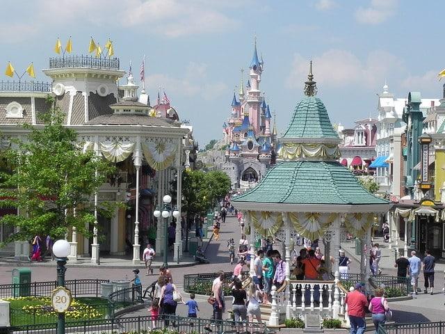 Na foto ve-se a entrada da Disneyland Paris com o castelo da bela adormecida ao fundo e pedestres - Foto: Betty Yobaccio