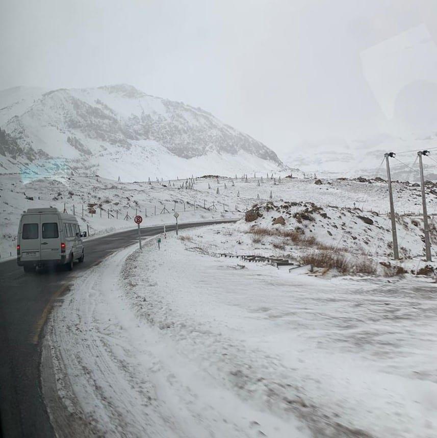 Vista de estrada para o Valle Nevado, com muita neve, placas e van andando na frente. Foto de Bruno Tavares.