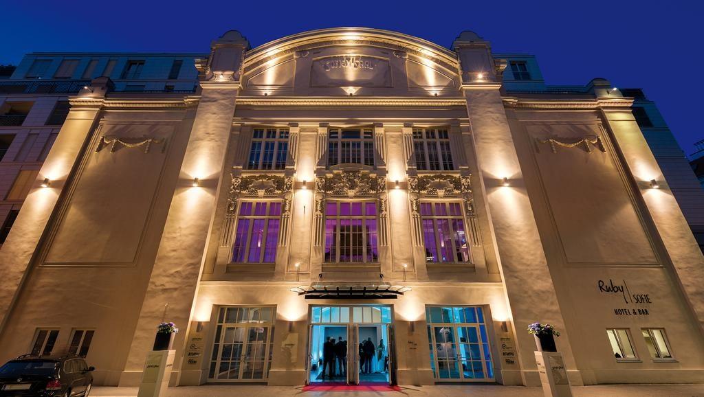 Vista da fachada do Ruby Sofie Hotel Vienna, com janelas grandes e luzes coloridas.
