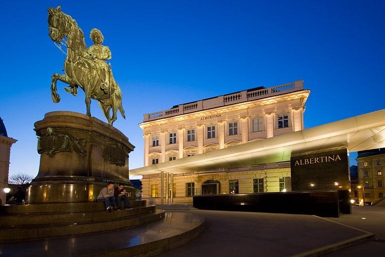 Área externa da Galeria Albertina com estátua na frente e céu bem azul ao fundo.
