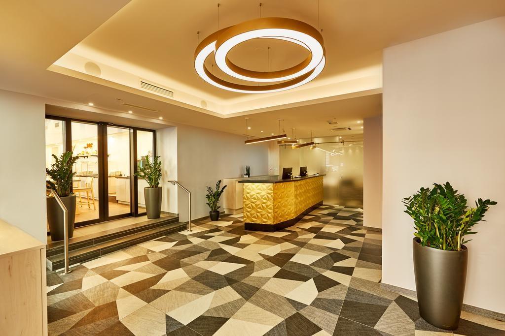 Vista do hall de entrada do H+ Hotel Wien, com carpete de estampa geométrica, lustre moderno arredondado, balcão de check-in, vasos de plantas e porta automática.