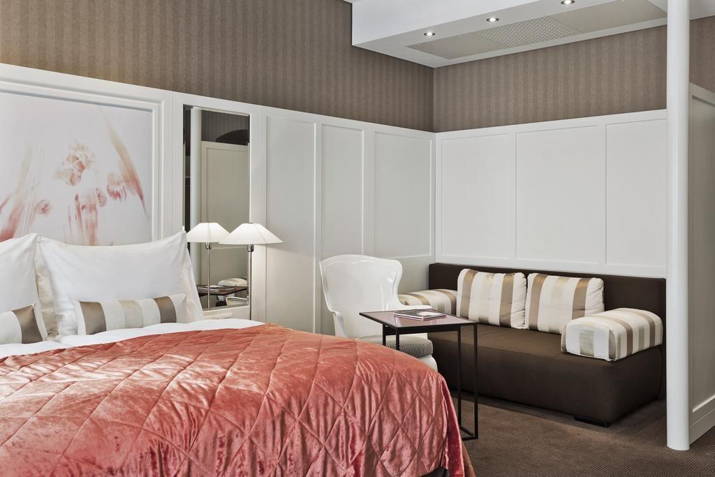 Foto de quarto do hotel The Harmonie Vienna, com cama de casal grande, cadeira, mesinha e sofá.