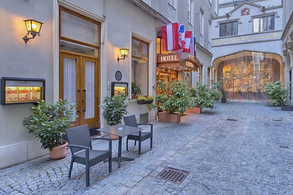Fachada do Hotel Austria - Wien, numa rua sem saída, com bandeiras de países na entrada.
