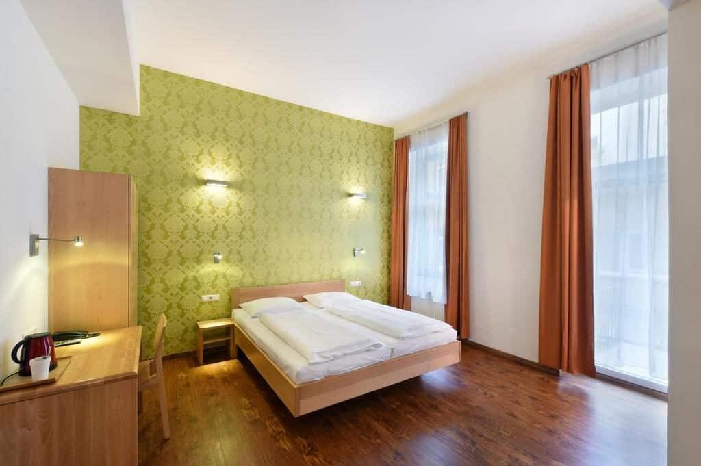 Quarto com cama de casal, papel de parede verde, janelas longas e cortinas no Hotel Mocca, para onde ficar em Viena.