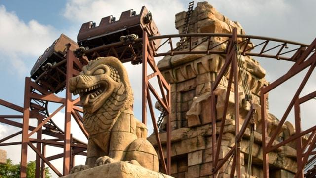 A montanha russa do Indiana Jones, com estatua de um leao e o looping ao fundo