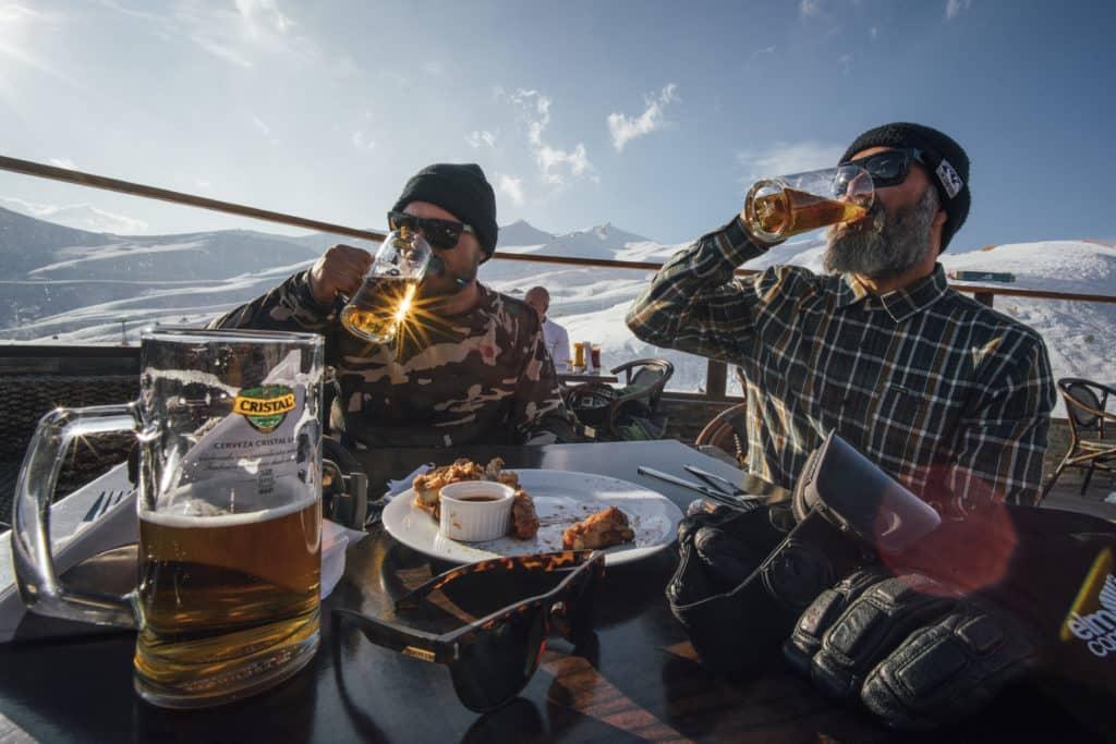 Dois esportistas de snowboard no terraço do restaurante La Leñera, opção de onde comer no Valle Nevado. Foto do site oficial.