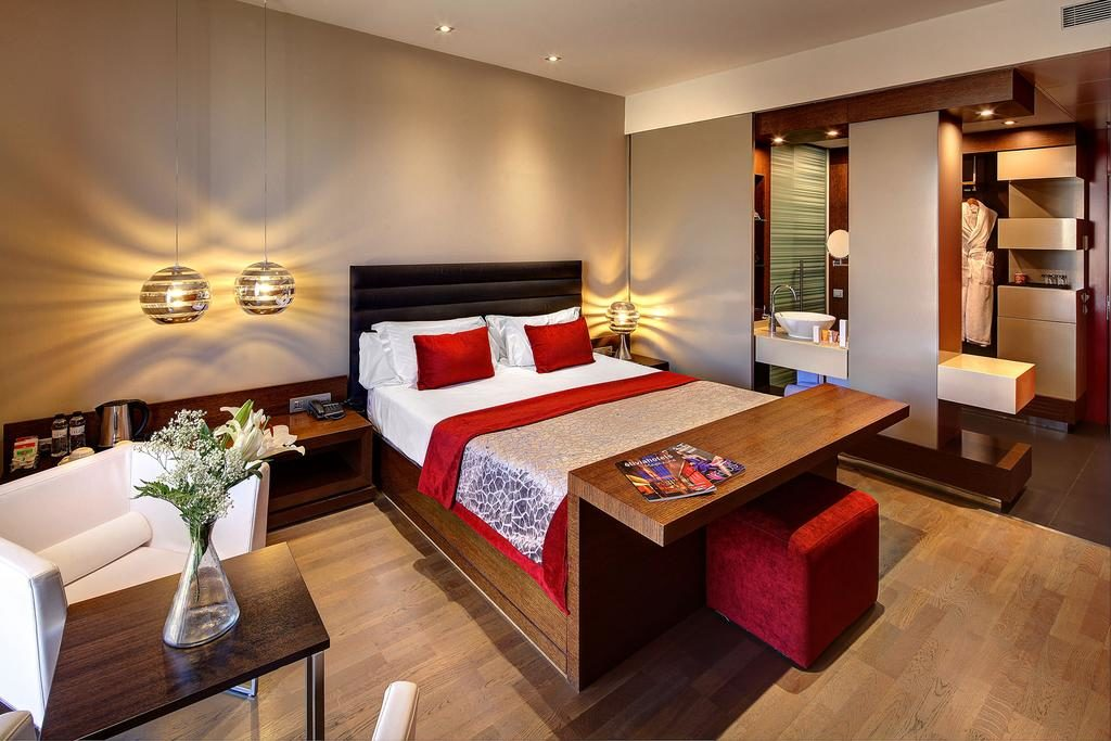 Quarto do olivia plaza hotel. Cama de casal com lençóis vermelho e branco e piso de madeira com iluminação confortável