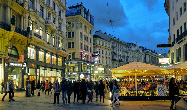 Vista de rua em Viena, com pessoas caminhando em volta de prédios da cidade, em post com dicas de onde ficar em Viena. Foto de Pedro Szekely
