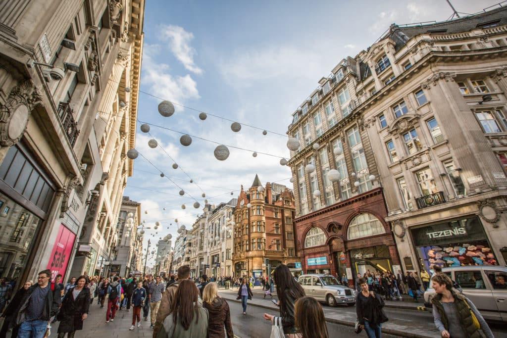 Uma dica imperdível do guia Londres pontos turísticos: visitar a famosa Oxford Street, famosa rua com lojas. Na foto vemos a rua com pessoas, decoração de luzes e prédios tradicionais. Foto de Tony Webster via Flickr