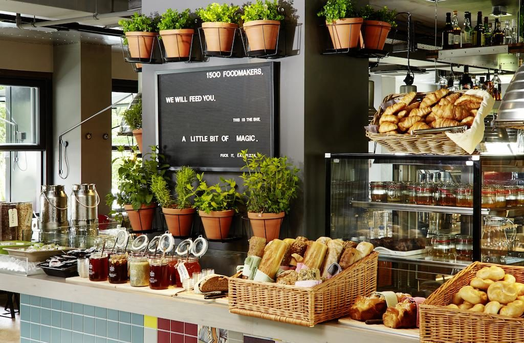 Foto de parque do 1500foodmakers, o restaurante do 25Hours Hotel, com cestas de pães e potes de geleia.
