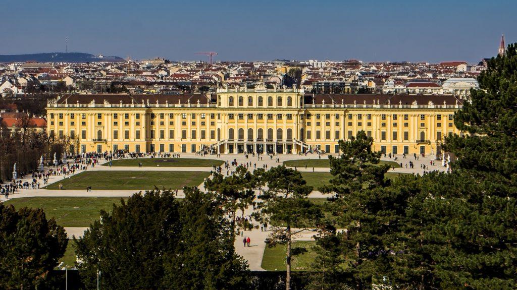 O imponente palácio Schönbrunn capturado de longe em uma foto que enquadra toda sua extensão.