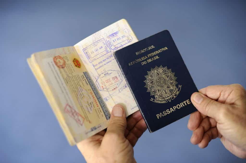 Mãos segurando passaporte brasileiro. Foto de Senado Federal via Flickr.