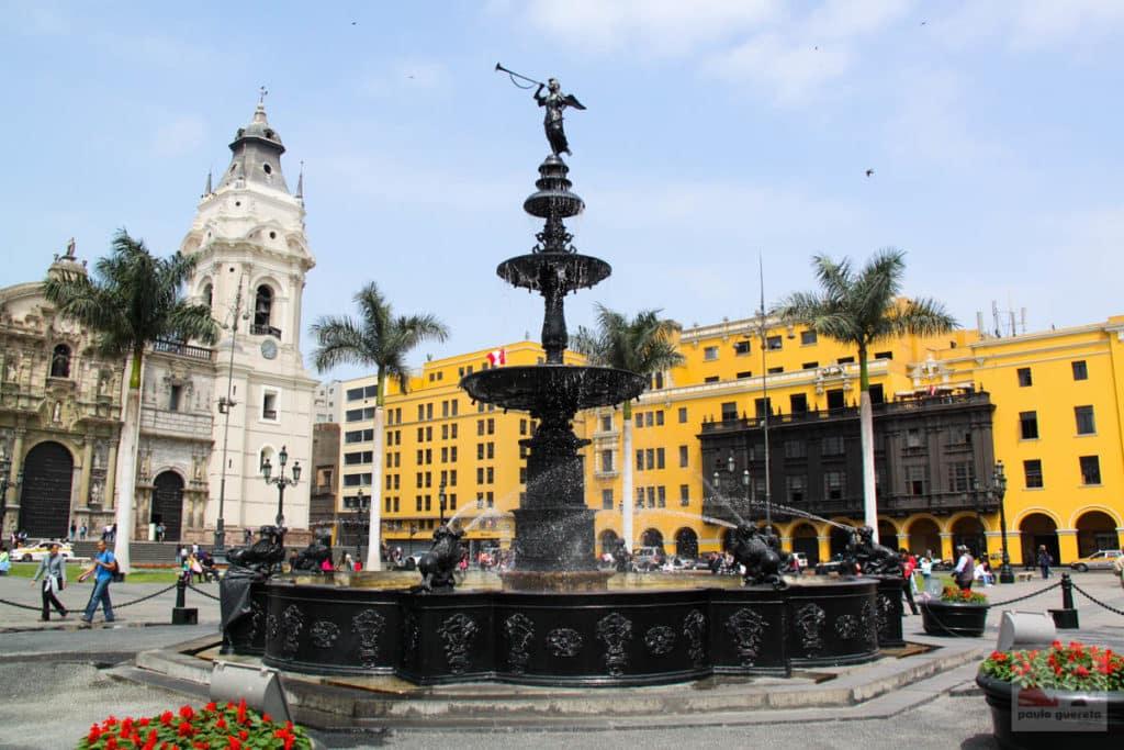 Vista de fonte no centro histórico de Lima, no Peru, em local chamado Plaza de Armas, com construções consideradas patrimônio ao fundo.