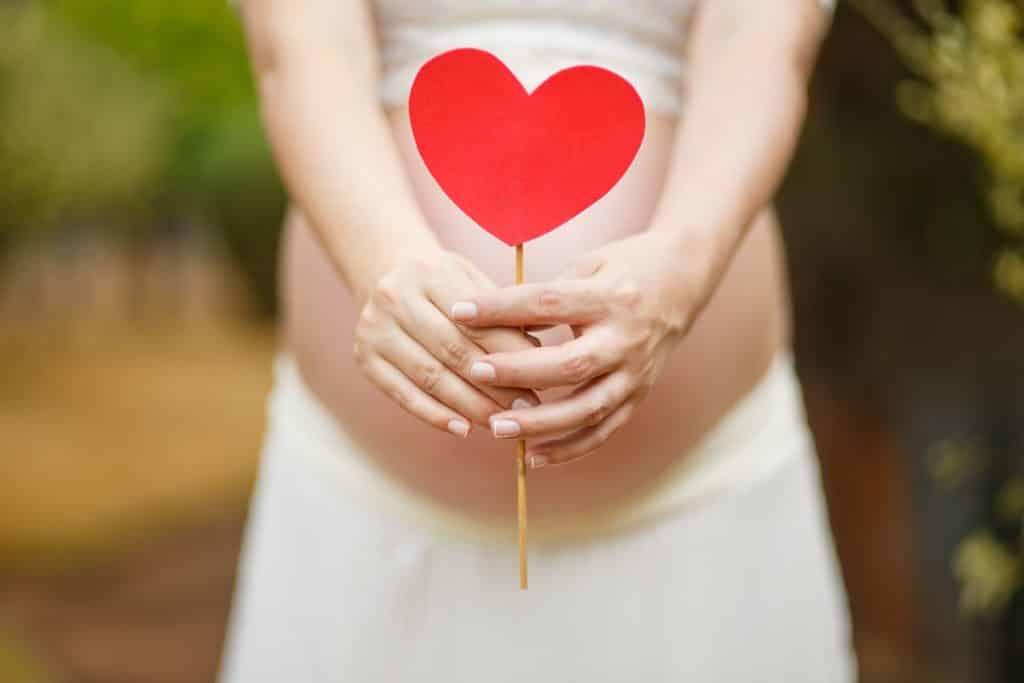 Mulher grávida de roupa branca segurando um coração de papel vermelho.
