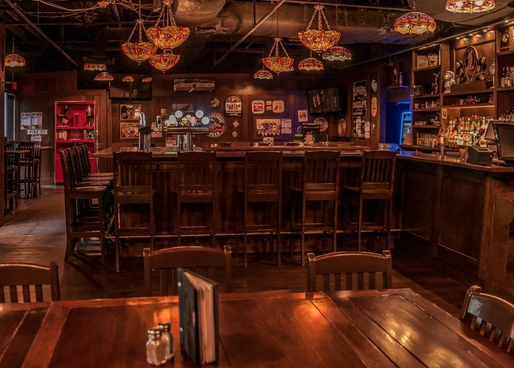 Na foto vemos a área interna de um típico pub inglês, com mesa, cadeiras, balcão e lustres, em iluminação fraca. Foto do site oficial Sherlocks Pubs.
