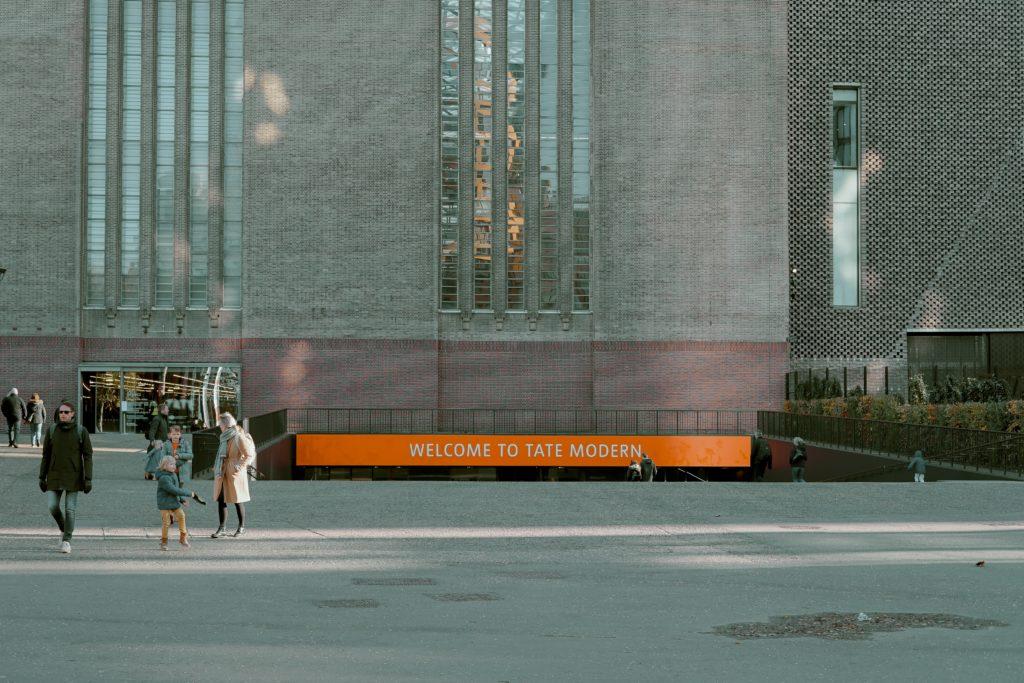 Vista de placa de boas-vindas na entrada do Tate Modern, em Londres. Foto de Toa Heftiba via Flickr.