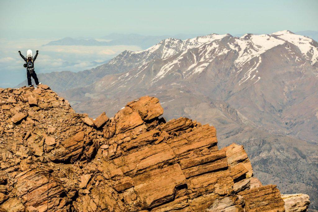 Pessoa no Valle Nevado em época quente, sem neve na montanha. Foto do site oficial Valle Nevado.