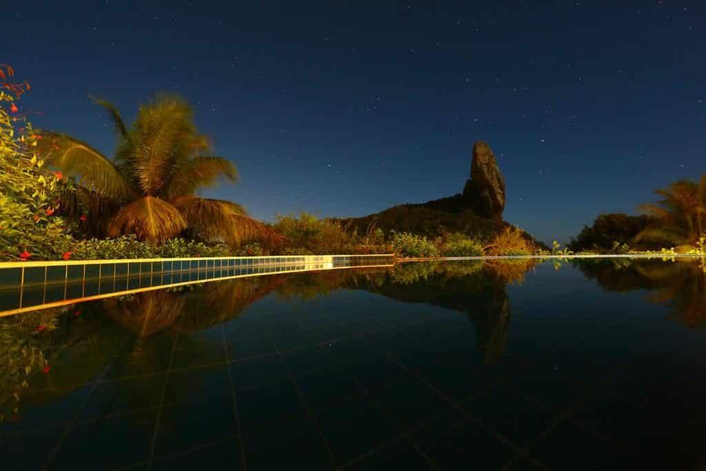 Piscina da Pousada Zé Maria à noite, com vista para rocha e vegetação nos arredores