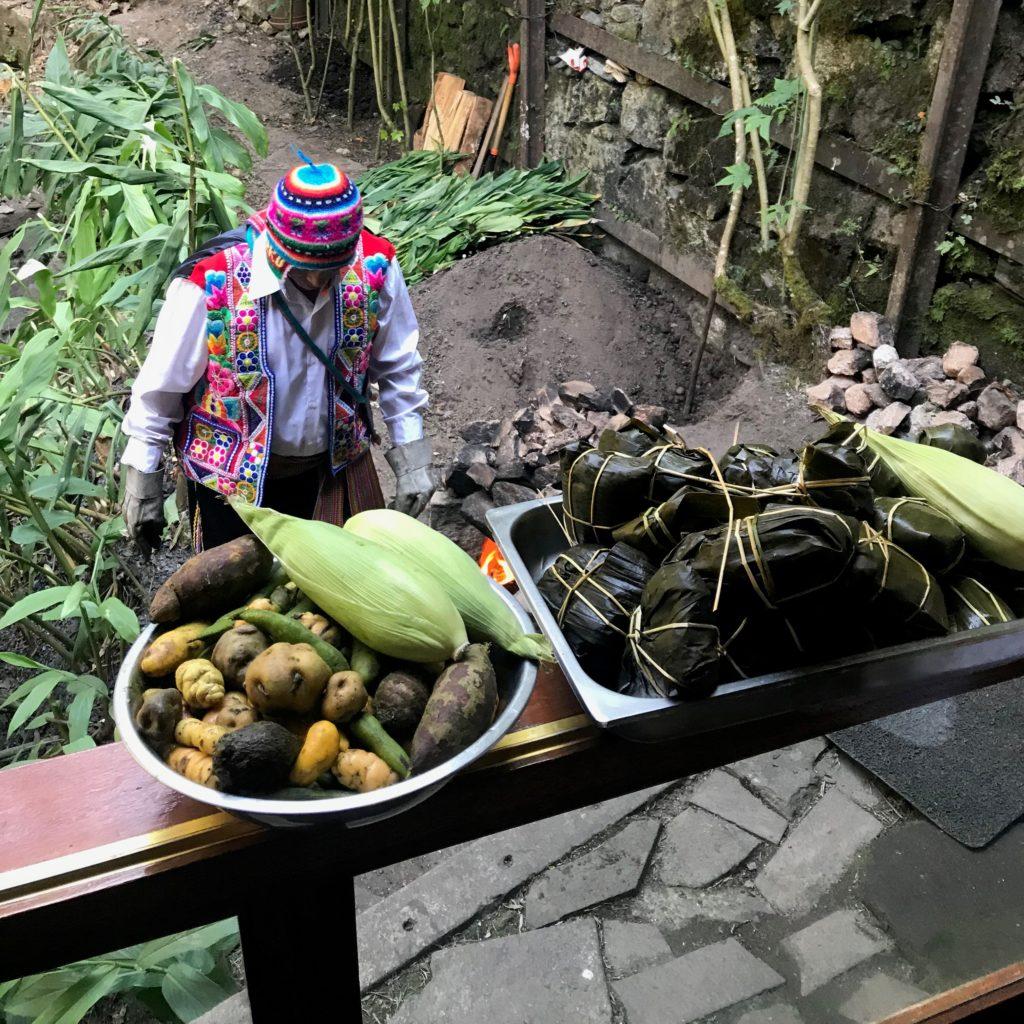 Foto com os alimentos para a refeição típica Pachamanca com funcionário ajeitando o solo