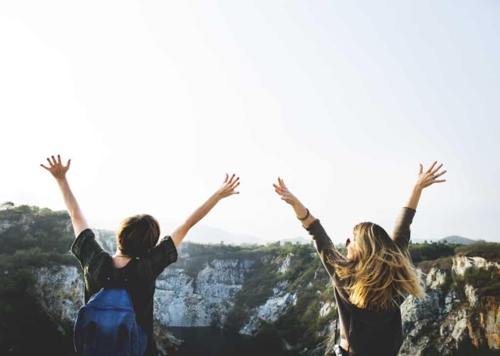 melhor seguro viagme europa - amigas com mão levantadas em cima de uma montanha