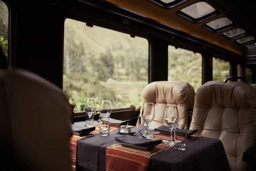 Assentos com mesa na primeira classe do Inca Rail.