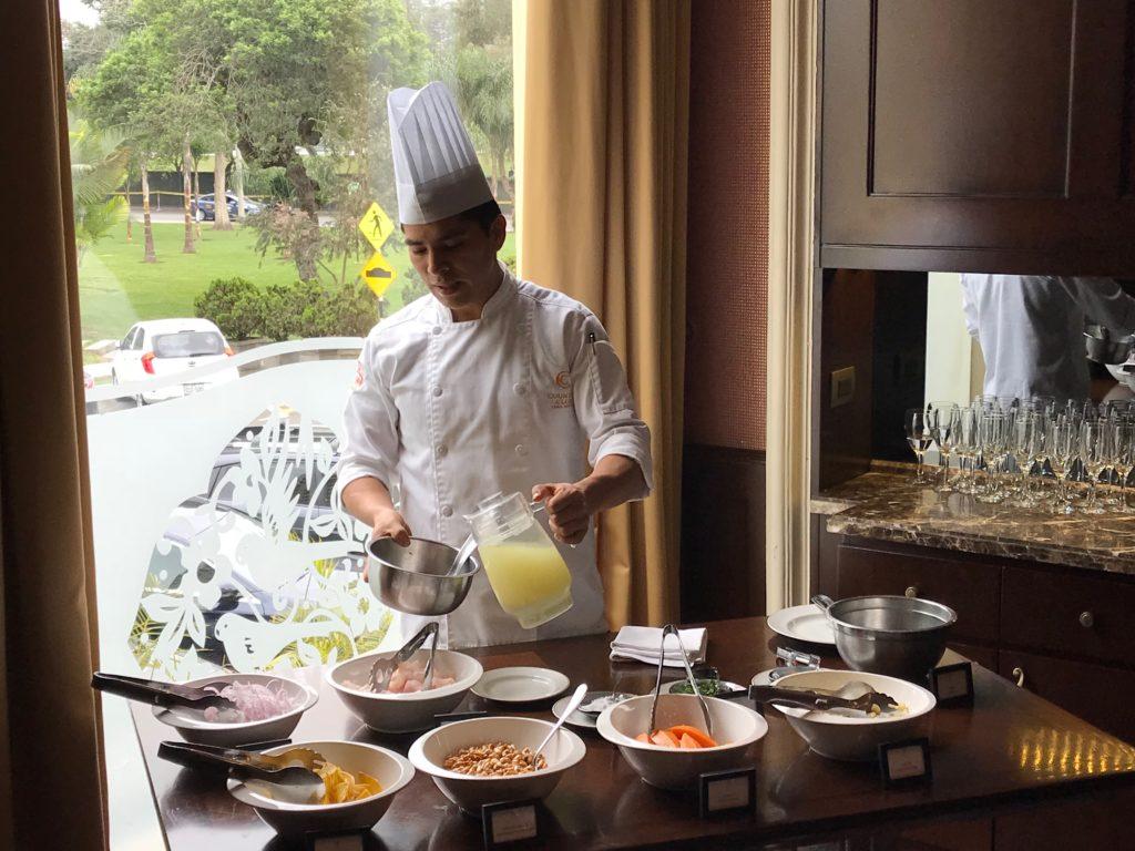 Chef de cozinha explica como fazer ceviche montando o prato com ingredientes frescos, postos em uma mesa e separados em tigelas.