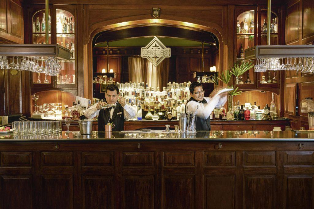 Dois bartenders preparam drinks no Bar Inglês do hotel.