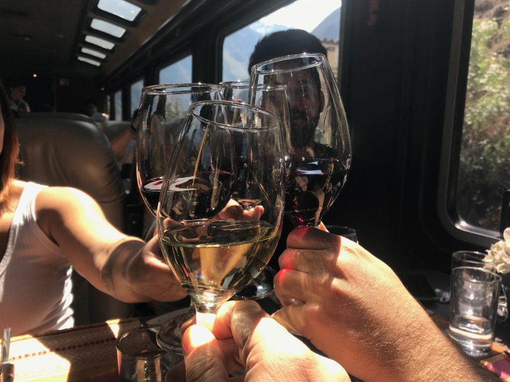 Foto de brinde com taças de vinho no Inca Rail, trem que faz o trajeto até Machu Picchu Pueblo.