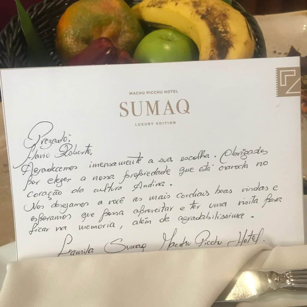 Carta escrita à mão no Sumaq, com cesta de frutas ao fundo.
