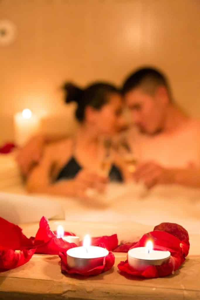 Casal em banheira com taças e luz de velas, uma ideia de presente de SPA para uma lua de mel em Lima